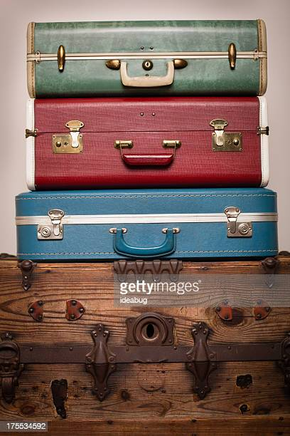 Three Retro Suitcases Stacked on Wood Trunk