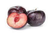 three ripe black plums isolated