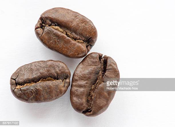 Three roasted coffee beans resting on top of white surface