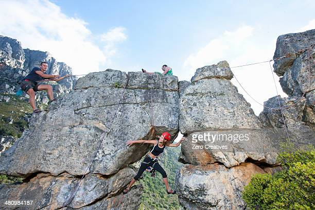 Three rock climbers climbing up rock formation