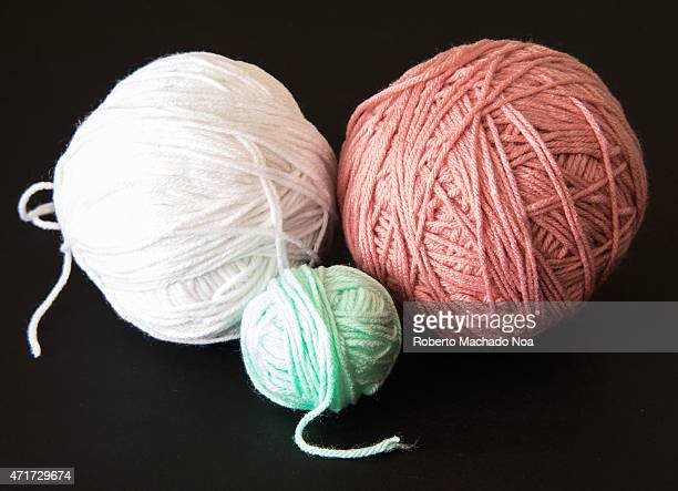 Three rolls or balls of worsted yarn of different color over a black background