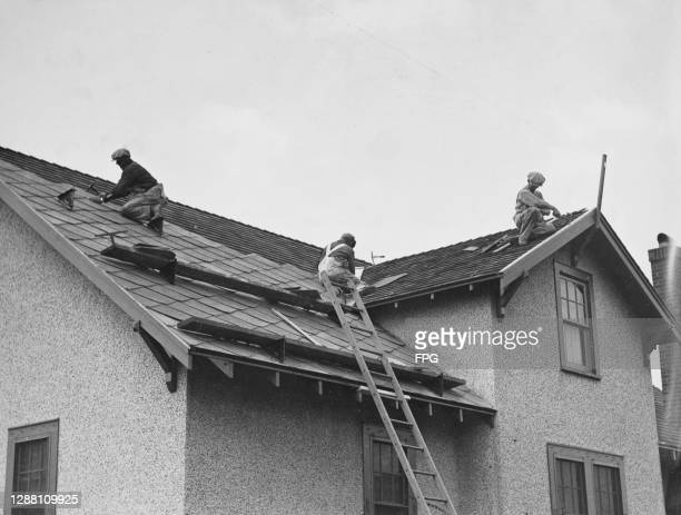 Three roofers at work on applying roof tiles to a property, a ladder leans against the building, leading to two horizontal supports for the roofers,...