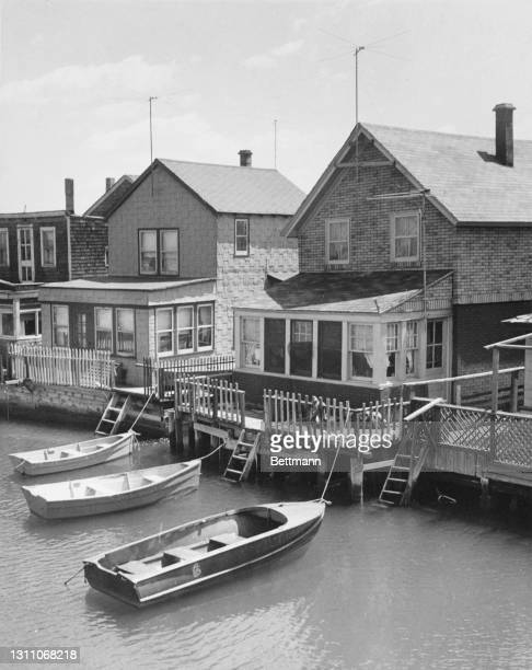 Three rowboats tethered at private mooring points to the rear of houses in the Ramblersville area of Howard Beach, a neighbourhood in the Queens...