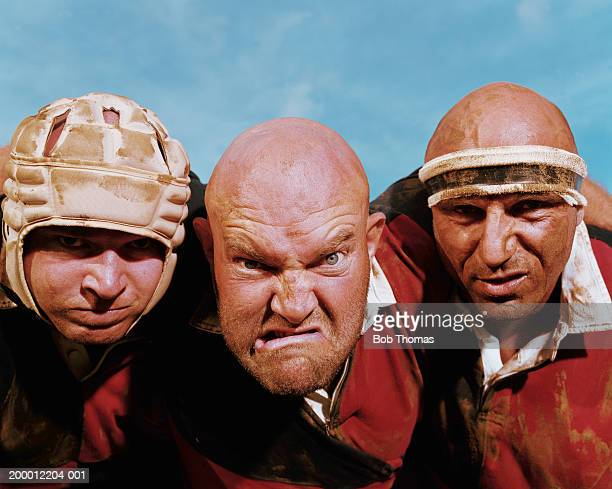three rugby players, man in centre pulling face, portrait, close-up - ugly bald man stock pictures, royalty-free photos & images