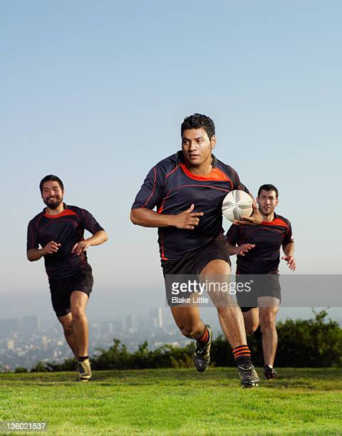 Three rugby players running on a field.