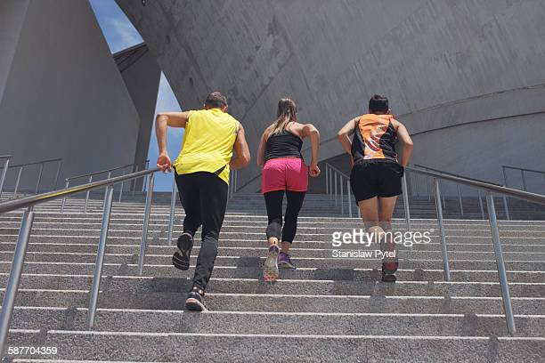 Three runners exercising on stairs