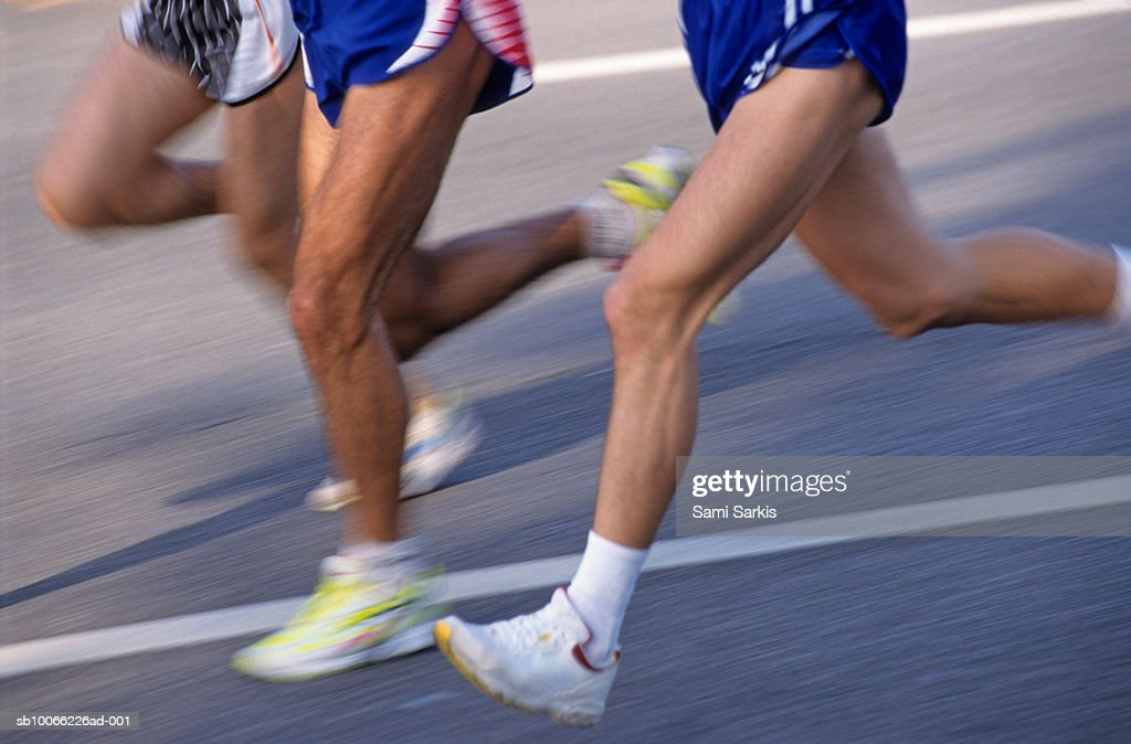 Three runners, low section (blurred motion) : Stock Photo