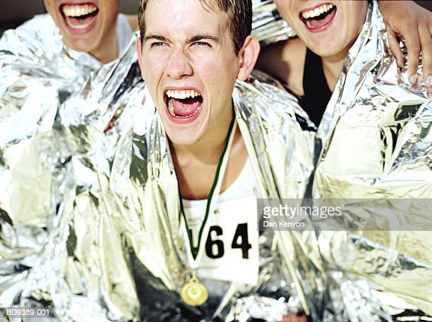 three runners wrapped in foil blankets, cheering, close-up - marathon stock pictures, royalty-free photos & images