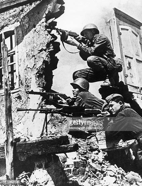 Three Russian soldiers lying in ambush amid the ruins of a building in Stalingrad . Stalingrad, October 1942