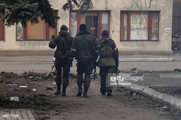Three Russianbacked separatist soldiers walk in the central square as Debaltseve copes with the aftermath of a siege and then capture by...