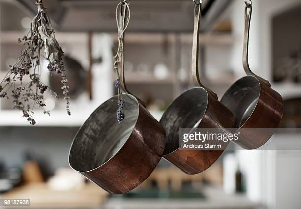 Three saucepans hanging from hooks with dried lavender