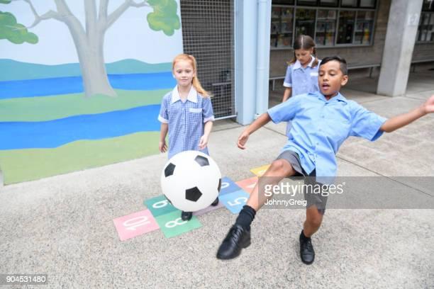 Drie kinderen van de school spelen in werf jongen schoppen Voetbal naar camera