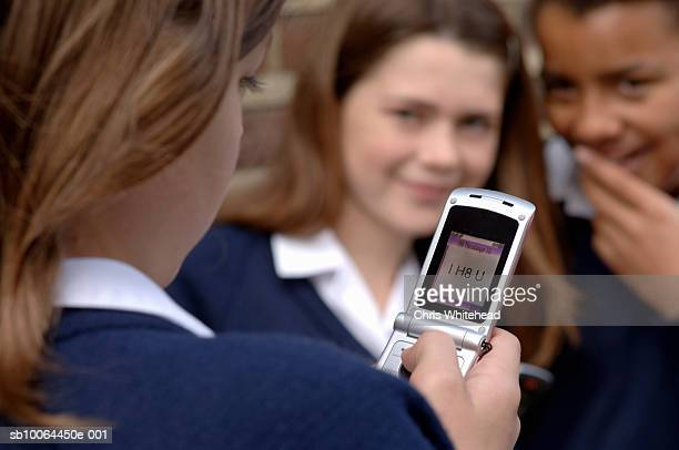 Three school girls (11-12), one reading text message that says 'I h8 u', focus on foreground