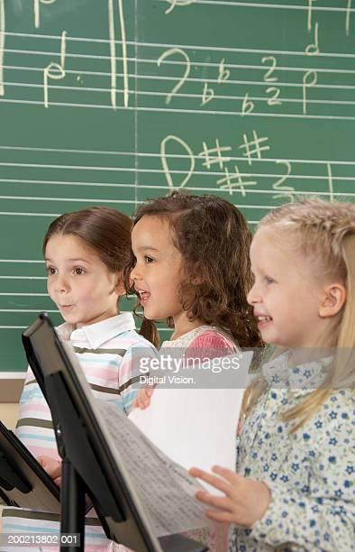 Three school girls (5-10) singing in class