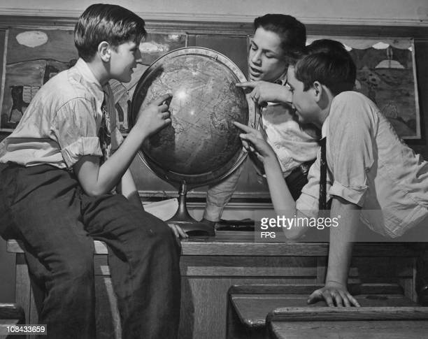 Three schoolboys pointing at globe in a classroom circa 1950