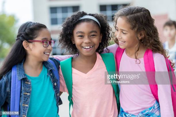 three schoolgirls embrace on first day of school - schoolgirl stock pictures, royalty-free photos & images