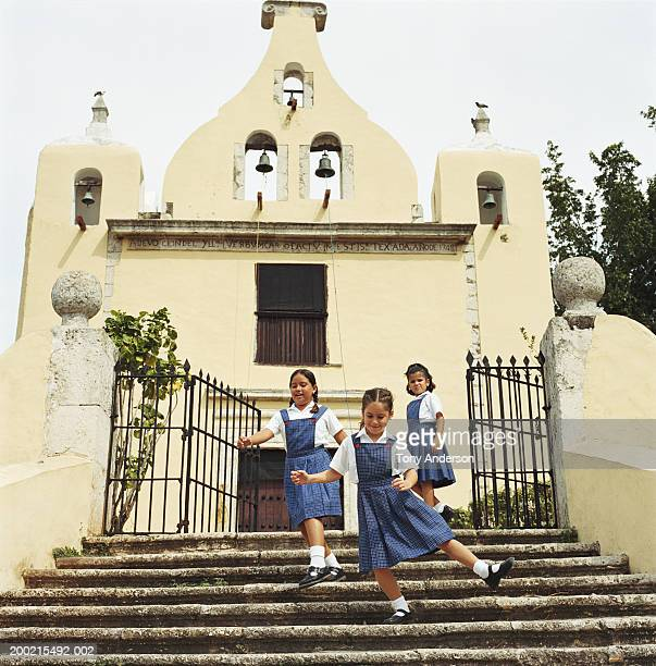 Three schoolgirls (5-9) playing on church steps