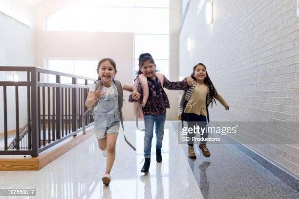 three schoolgirls running in school hallway - state school stock pictures, royalty-free photos & images