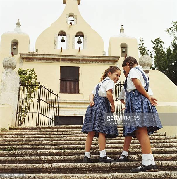 Three schoolgirls (5-9) talking on church steps