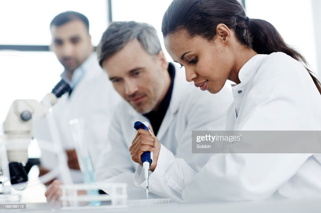Three scientists examining samples in a laboratory : Stock Photo