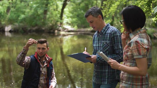 Three scientists exploring water in lake 696272668