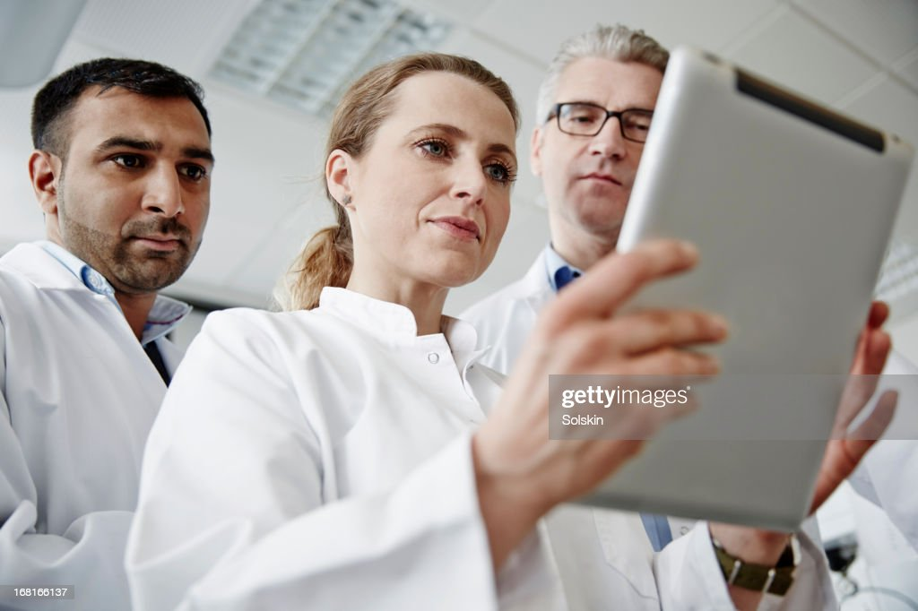 Three scientists in a laboratory, using tablet : Stock Photo
