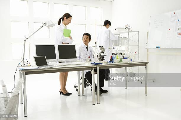 Three scientists in laboratory, front view, side view, rear view