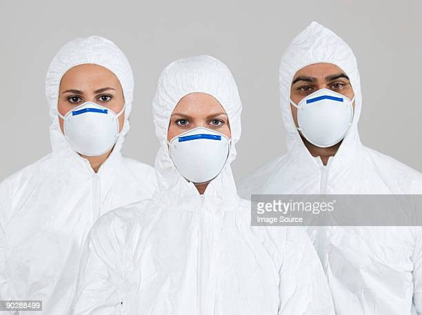 three scientists wearing protective suits - protective suit stock pictures, royalty-free photos & images