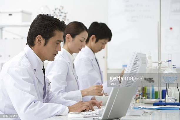 Three scientists working at the desk, woman holding mortar and pestle, side view, differential focus
