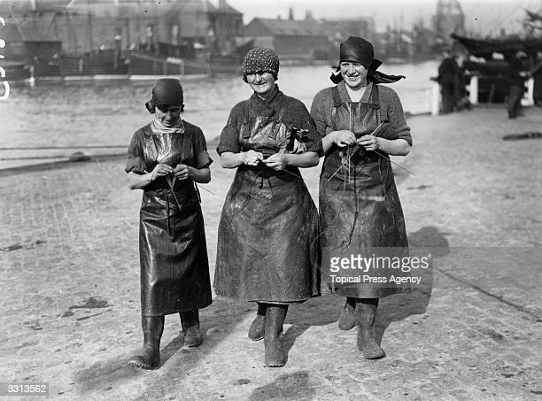 Three Scottish herring girls knitting whilst waiting for the arrival of the fishing fleet at Great Yarmouth in England Thousands of women travel from...