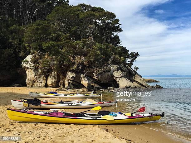 Three sea kayaks on beach at Watering Cove, Abel Tasman National Park, New Zealand