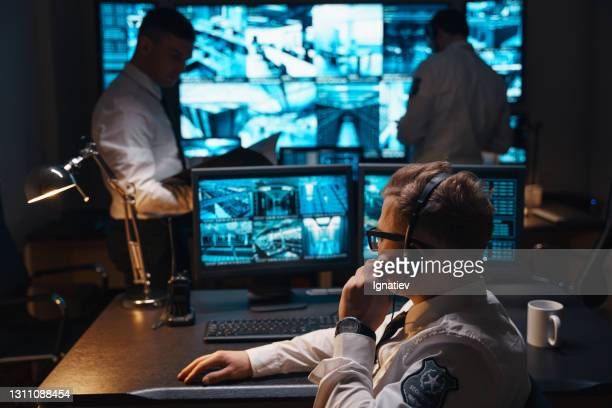 three security officers are working to protect the facility and ensure security. - police station stock pictures, royalty-free photos & images