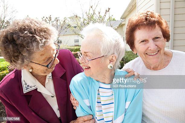 Three Senior Adult Women Laughing Together Outside in Courtyard