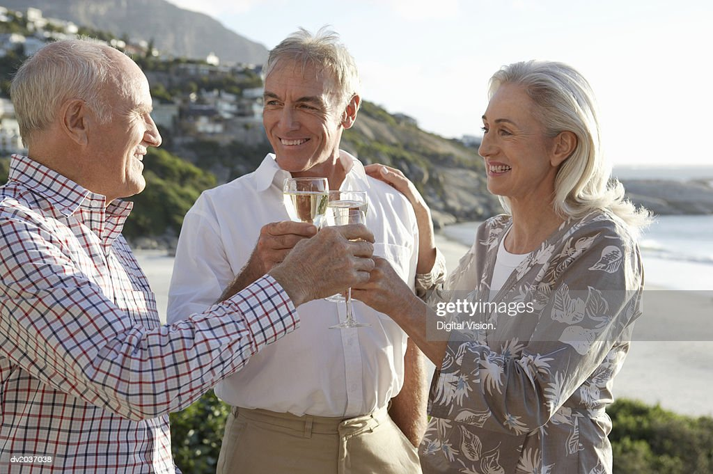 Three Senior Adults Having a Champagne Toast at the Coast : Stock Photo