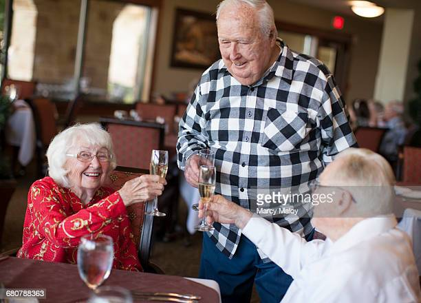 Three senior adults in restaurant, holding champagne glasses, making toast