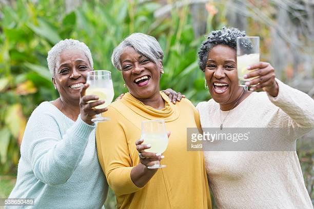 Three senior African American woman toasting