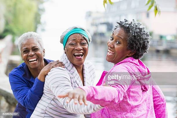 Three senior black women laughing together outdoors