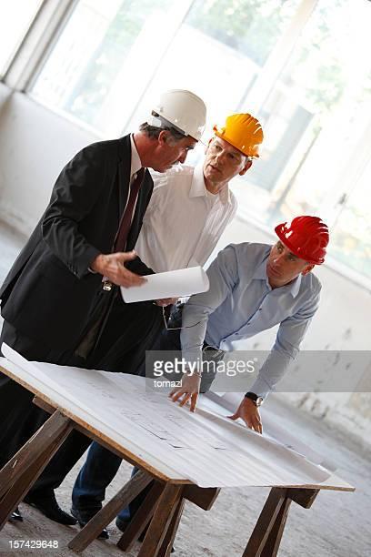 Three senior business men at construction site