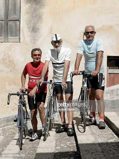 Three senior cyclists posing with bikes on staircase in old town, portrait
