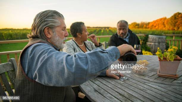 Three senior friends drinking the red wine at the winery