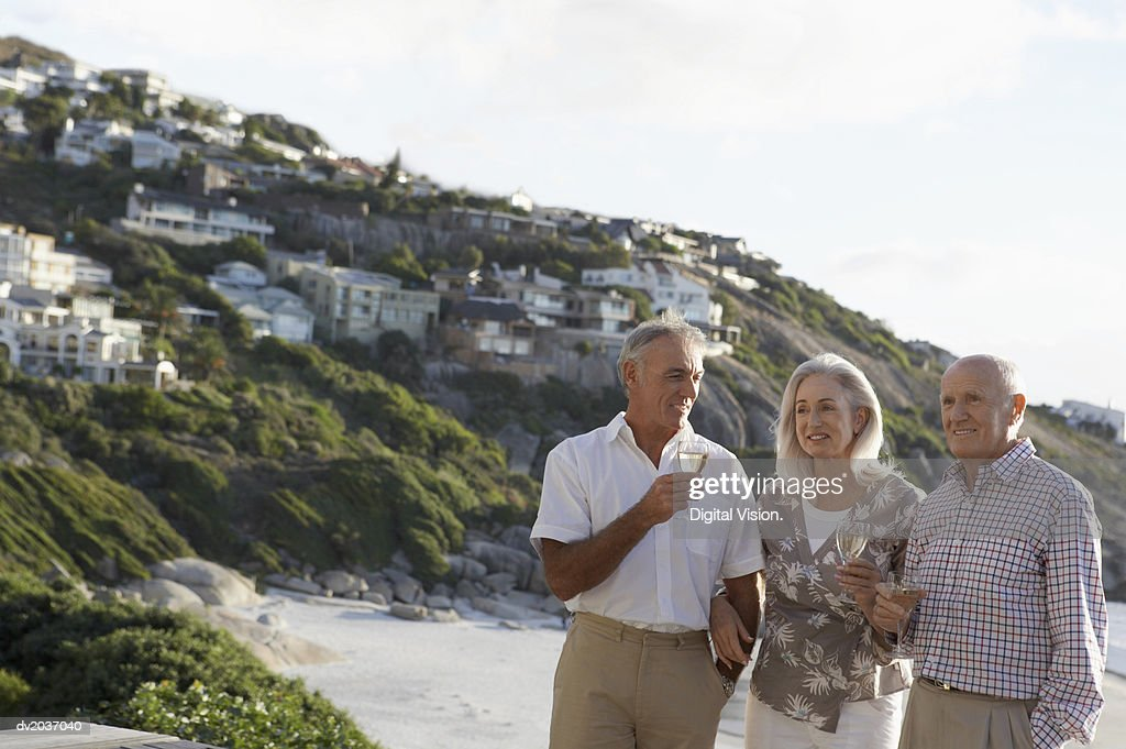Three Senior Friends Enjoying White Wine on a Beach : Stock Photo