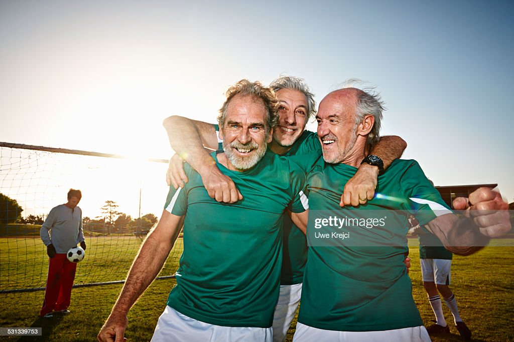 Three senior male soccer players celebrating : Stock Photo