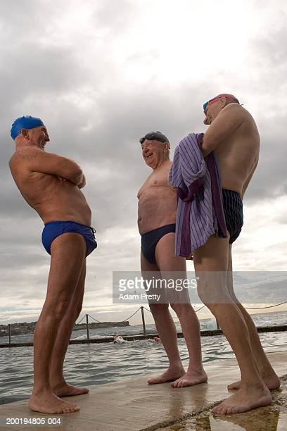 Three senior men at side of infinity pool, laughing, low angle view