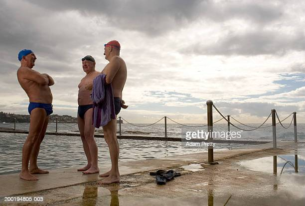 three senior men at side of infinity pool, laughing - male friendship stock pictures, royalty-free photos & images