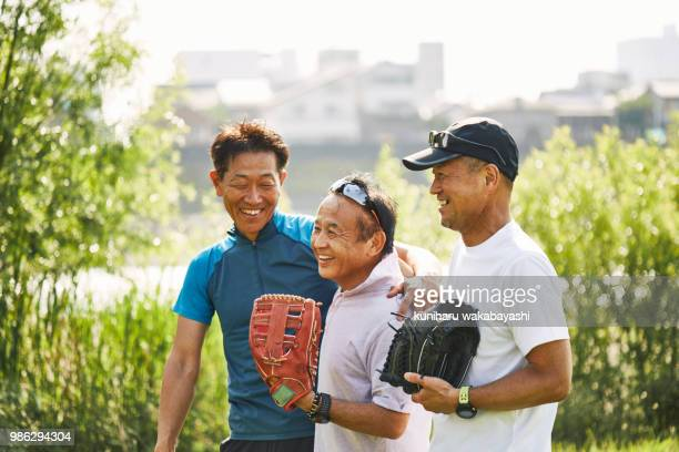 three senior men before or after playing baseball in a park - スポーツ  ストックフォトと画像