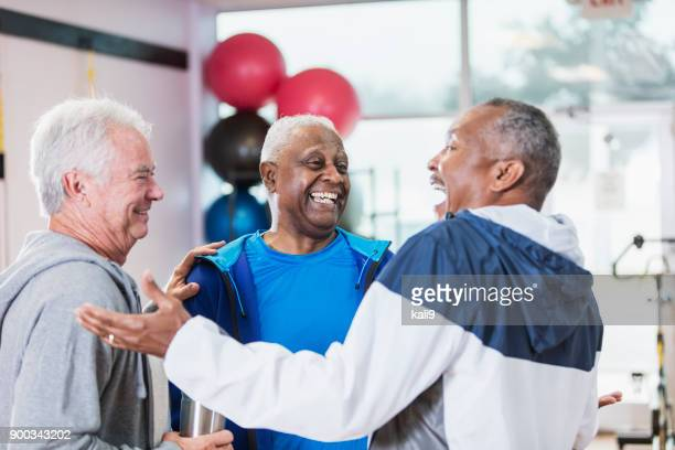 three senior men hanging out at gym, talking - african american man helping elderly stock pictures, royalty-free photos & images