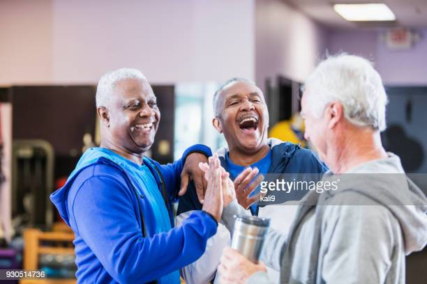 Three senior men hanging out at gym, talking