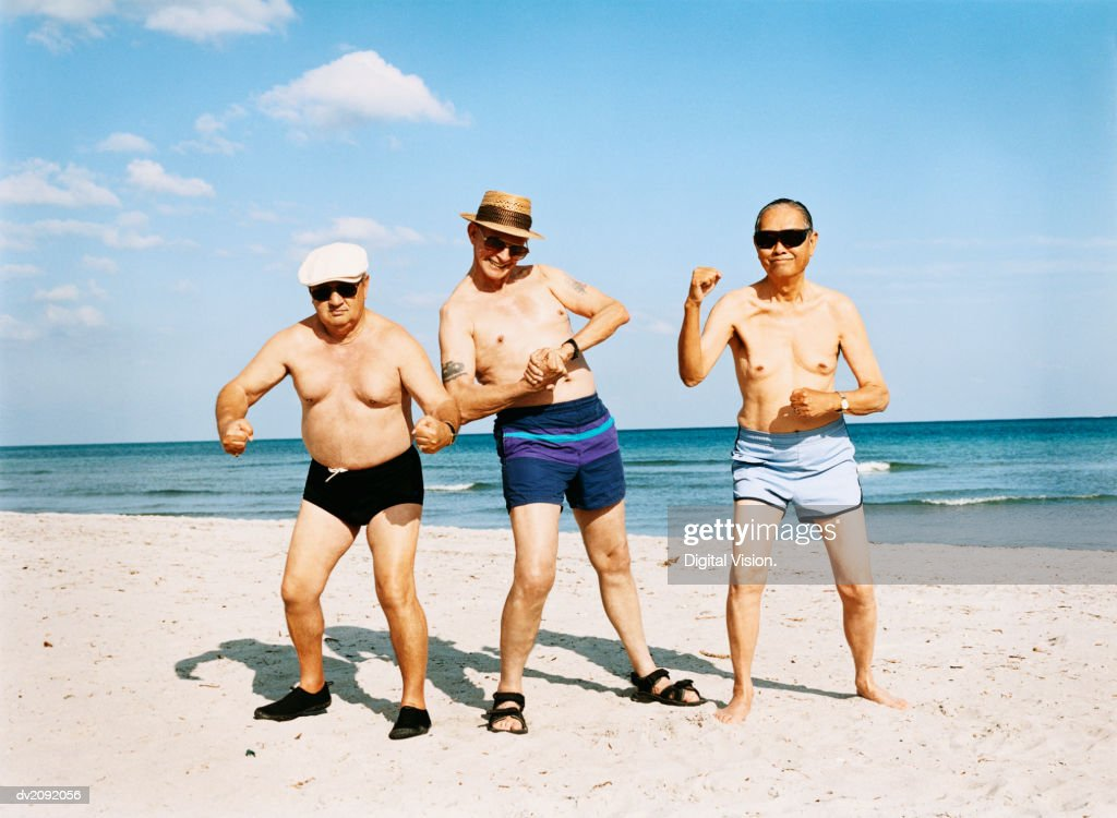Three Senior Men in Swimming Trunks Stand on the Beach Flexing Their Muscles