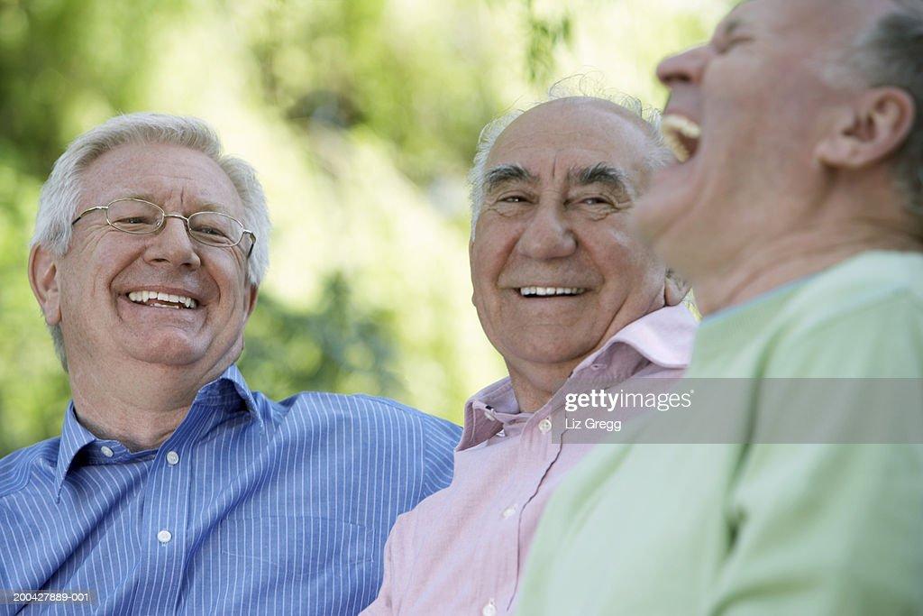 Three senior men laughing, close-up (focus on man wearing glasses) : Stock Photo