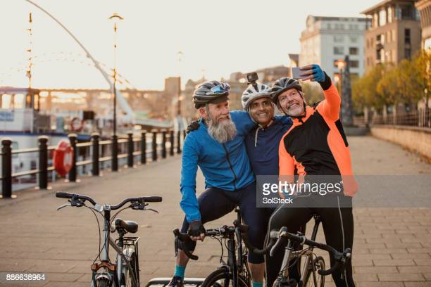 three senior men on racing bikes taking a selfie - waterfront stock pictures, royalty-free photos & images